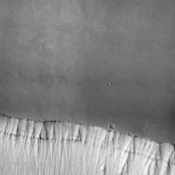 At the bottom of this image from NASA's Mars Odyssey is the cliff-face that is the sidewall of Ophir Chasma. Layering is easily visible in the upper cliff wall, with the thickness of the surface clearly visible.