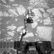 NASA's Mars Exploration Rover Opportunity used its rock abrasion tool on a rock informally named 'Gagarin,' leaving a circular mark. At the end of the rover's arm, the tool turret is positioned with the rock abrasion tool pointing upward.