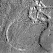 This image captured by NASA's 2001 Mars Odyssey of Elator Vallis shows where a crater has deflected flow and created a streamlined island.