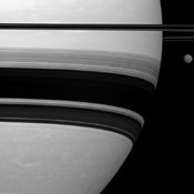 Saturn's largest moon, Titan, looks small here, pictured to the right of the gas giant as seen by NASA's Cassini spacecraft.