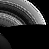 NASA's Cassini spacecraft shows Saturn's shadow cutting sharply across its rings as the orbits of ring particles carry them suddenly from day to night. With no atmosphere to scatter light, shadows in space are much darker than we're used to here on Earth.