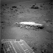 Part of NASA's Mars Exploration Rover Opportunity's array of photovoltaic cells is visible in the foreground of this image. Opportunity took this picture showing a light-toned rock,