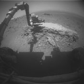 NASA's Mars Exploration Rover Opportunity used its front hazard-avoidance camera to take this picture showing the rover's arm extended toward a light-toned rock,