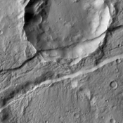The downdropped block of surface seen in this image captured by NASA's 2001 Mars Odyssey spacecraft is called a graben. The graben is younger than the crater, since the crater is cut by the graben.