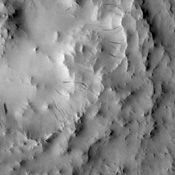 Dark slope streaks are visible on the rim of this unnamed crater located on the floor of Cassini Crater in this image from NASA's 2001 Mars Odyssey spacecraft.