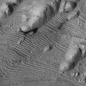 Rhythmic patterns of sedimentary layering in Danielson Crater on Mars result from periodic changes in climate related to changes in tilt of the planet in this image was taken by NASA's Mars Reconnaissance Orbiter.