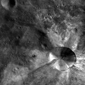 In this image from NASA's Dawn spacecraft, bright material extends out from the crater Canuleia on asteroid Vesta. The bright material appears to have been thrown out of the crater during the impact that created it.