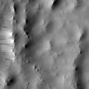 Dark streaks mark the inner rim of this unnamed crater in Terra Sabaea as seen by NASA's 2001 Mars Odyssey spacecraft.