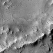 Dark slope streaks mark the rim of this unnamed crater withing Tikhonravov Crater in Terra Sabaea as seen by NASA's 2001 Mars Odyssey spacecraft.