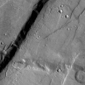 The cliff face in this image from NASA's 2001 Mars Odyssey spacecraft was created by tectonic activity and is located in a region of Tempe Terra that is complexly fractured.