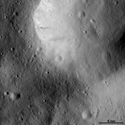 This image from NASA's Dawn spacecraft of asteroid Vesta shows hows a large impact crater whose rim is rather smoothed and degraded. There are many smaller, younger craters surrounding and inside of this crater and these have sharper, fresher rims.