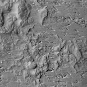 This image captured by NASA's 2001 Mars Odyssey spacecraft shows the complexity of wind erosion on Mars. The erosion of the hills and the gouge-like pits indicate two, if not three wind directions that all altered the surface.
