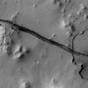 The fracture is this image captured by NASA's 2001 Mars Odyssey spacecraft cuts right through a hill, indicating tremendous tectonic stresses were at work to create this feature.