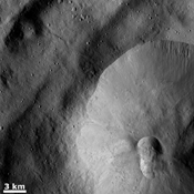 A double crater, called a crater doublet, is seen in the bottom right part of this image from NASA's Dawn spacecraft of asteroid Vesta. This crater doublet was likely formed by the simultaneous impact of two fragments of a split projectile.