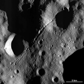 This image of asteroid Vesta from NASA's Dawn spacecraft is dominated by a chain of secondary craters located in Vesta's Floronia quadrangle, in Vesta's northern hemisphere.