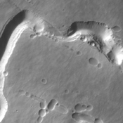 This image captured by NASA's 2001 Mars Odyssey spacecraft shows part of the southern flank of Pavonis Mons. Visible at the bottom of the image are collapse features and lava channels.