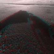 This image is a 3-D view in front of NASA's Curiosity rover captured by the rover's front left Hazard-Avoidance camera. The image is cropped but part of Mount Sharp is still visible rising above the terrain.