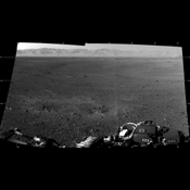 These are the first two full-resolution images of the Martian surface from the Navigation cameras on NASA's Curiosity rover, which are located on the rover's 'head' or mast. The rim of Gale Crater can be seen in the distance beyond the pebbly ground.
