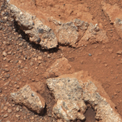 In this image from NASA's Curiosity rover, a rock outcrop called 'Link' pops out from a Martian surface that is elsewhere blanketed by reddish-brown dust.