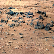 This patch of windblown sand and dust downhill from a cluster of dark rocks is the 'Rocknest' site, which has been selected as the likely location for first use of the scoop on the arm of NASA's Mars rover Curiosity.