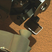 This image from a video shows the first Martian material collected by the scoop on the robotic arm of NASA's Mars rover Curiosity. The material vibrated inside the scoop after it was lifted from the ground.