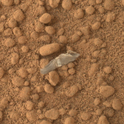 This image from NASA's Mars rover Curiosity shows a small bright object on the ground beside the rover at the 'Rocknest' site. The rover team has assessed this object as debris from the spacecraft, possibly from the events of landing on Mars.