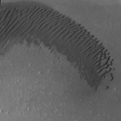 An arc of dunes covers part of the floor of this unnamed crater in Aonia Terra, as shown in this image captured by NASA's 2001 Mars Odyssey spacecraft.