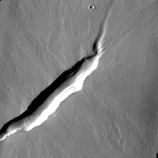 The linear depression in this image from NASA's 2001 Mars Odyssey spacecraft is a volcanic vent in the lava plains east of Pavonis Mons.