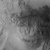 Continuing westward, this image from NASA's Mars Odyssey spacecraft shows Mt. Sharp just east of the highest peak of the deposit. The dark material near the top of the image is likely sand. This image shows the dark material on the floor and on Mt. Sharp.