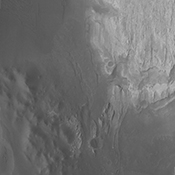 This image from NASA's Mars Odyssey spacecraft shows dark material at the bottom of the image, likely deposited by the large channel. It shows how close that material is to Mt. Sharp and how different the two deposits appear in a visible wavelength image.