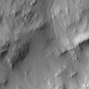 This image from NASA's Mars Odyssey spacecraft shows the southeastern rim of Gale Crater. The large ridge at the bottom of image is the top of the rim. Image shows a channel dissecting the rim; two dune fields occur along the path of the channel too.