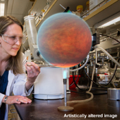 In this image, an artistic version of a hot Jupiter inspired by computer simulations has been inserted into a photo showing a Spitzer researcher, Heather Knutson, in a laboratory.