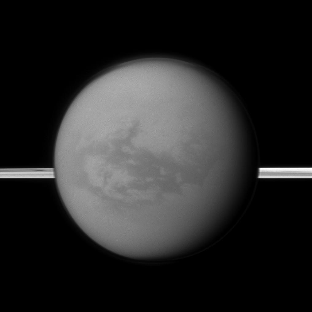 Saturn's rings lie in the distance as the Cassini spacecraft looks toward Titan