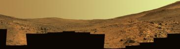 This panorama shows two reddish-brown, rock-strewn slopes on the left and right sides of a broad, U-shaped dip in the middle. In the distance are the broad slopes of 'McCool Hill.' Above that is an orangish-yellow sky.