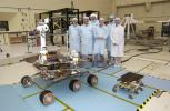 Members of the Mars Exploration Rovers Assembly, Test and Launch Operations team gather around NASA's Rover 2 and its predecessor, a flight spare of the Pathfinder mission's Sojourner rover, named Marie Curie.