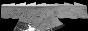 NASA's Mars Exploration Rover Spirit finished a drive and shows 'Bonneville' crater and the rocky plains surrounding it. The rover's solar panels are visible in the foreground, and the to right, the Columbia Hills complex.