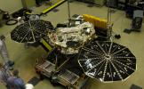 In this photograph of NASA's Phoenix Mars Lander, the spacecraft specialists worked on the lander after its fan-like circular solar arrays had been spread open for testing.