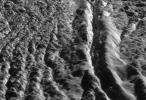 This perspective view, generated from high resolution images acquired by NASA's Cassini orbiter, highlights one of the wall scarps of the medial trough of Damascus Sulcus on Enceladus.