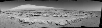 A landscape scene from NASA's Curiosity Mars rover shows rock rows at 'Junda' forming striations in the foreground, with Mount Sharp on the horizon.