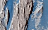 This is a close-up from NASA's Mars Reconnaissance Orbiter spacecraft of the western Medusa Fossae formation where we can see dust-covered rocky, bedrock surfaces (beige) and a bluish-tinted sand sheet that transitions into several dunes.