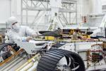 An engineer works on attaching NASA's Mars Helicopter to the belly of the Mars 2020 rover, which has been flipped over for that purpose, on Aug. 27, 2019, at the Jet Propulsion Laboratory in Pasadena, California.